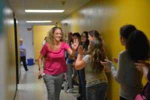 Beth Houf high-fiving students after being named Missouri National Distinguished Principal.