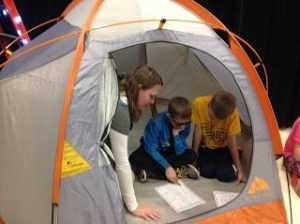 Amber Ernst in tent with students and classwork