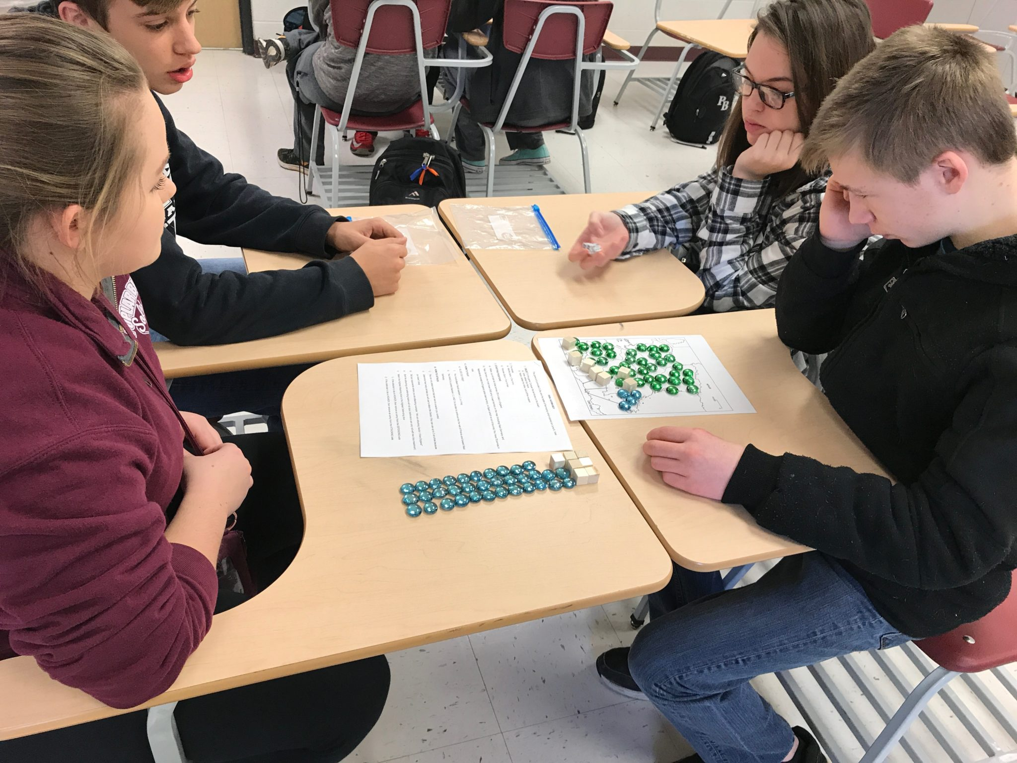 Students working in industrialization simulation with marbles representing items on an assembly line